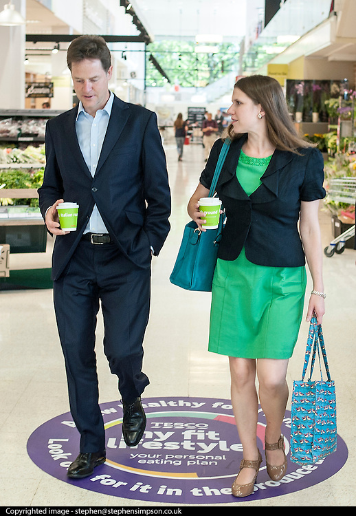 ***EMBARGO UNTIL 0001 FRIDAY 18th JULY 2014***© Licensed to London News Pictures. 16/07/2014. London, UK. NICK CLEGG and JO SWINSON leave the store with drinks.  Deputy Prime Minister and Leader of the Liberal Democrats Nick Clegg visits Tesco in Kensington to meet staff along with Jo Swinson. The Liberal Democrats will say in their 2015 manifesto that they will require large companies to publish the average salary of their male and female employees, increasing public pressure for equal pay. Tesco are one of the companies that currently publish this information voluntarily under the Government's Think, Act, Report scheme.. Photo credit : Stephen Simpson/LNP