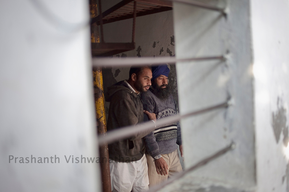 "A drug addict is led to the doctor by another inmate at ""Navjeevan""drug rehabilitation center in Amritsar, India, on Wednesday, December 15, 2010. Photographer: Prashanth Vishwanathan/HELSINGIN SANOMAT"