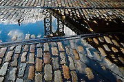 Reflection of the Manhattan bridge in a puddle on a street of DUMBO, Brooklyn, New York, 2008.