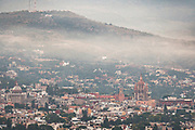 Morning fog rises over the colonial center and city landmark Parroquia de San Miguel Arcángel church in San Miguel de Allende, Mexico at dawn.
