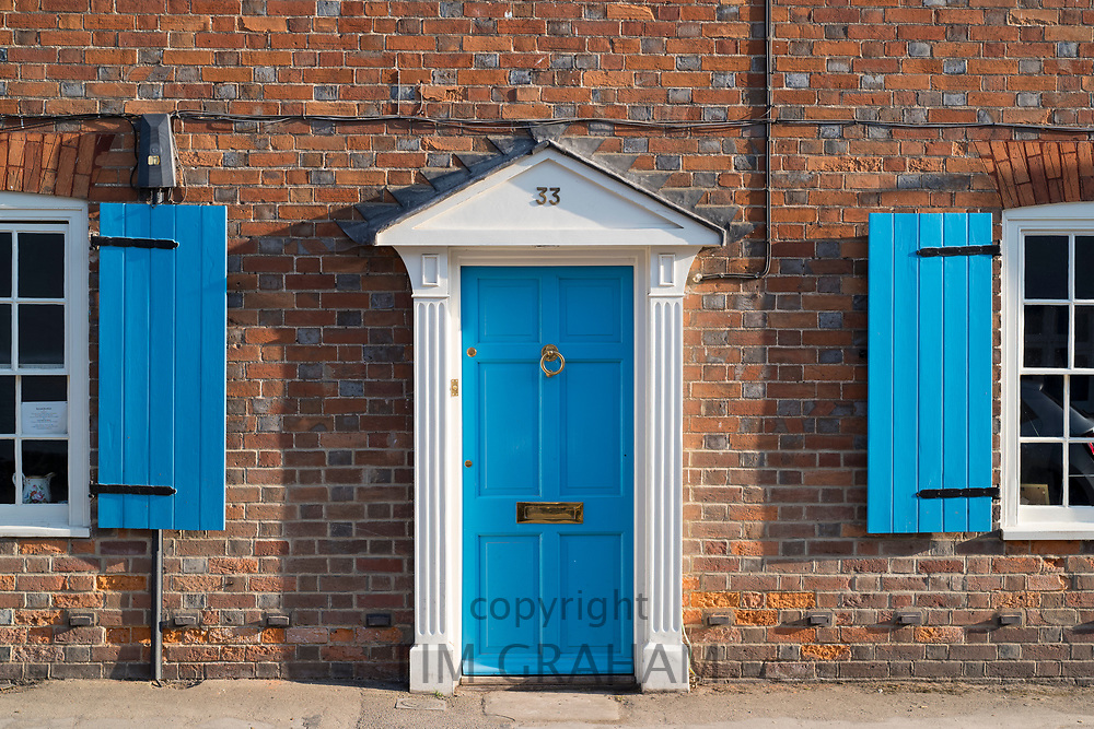 Quaint door and windows painted bright blue of brick built English cottage with portico and shutters in Ramsbury, Wiltshire, UK