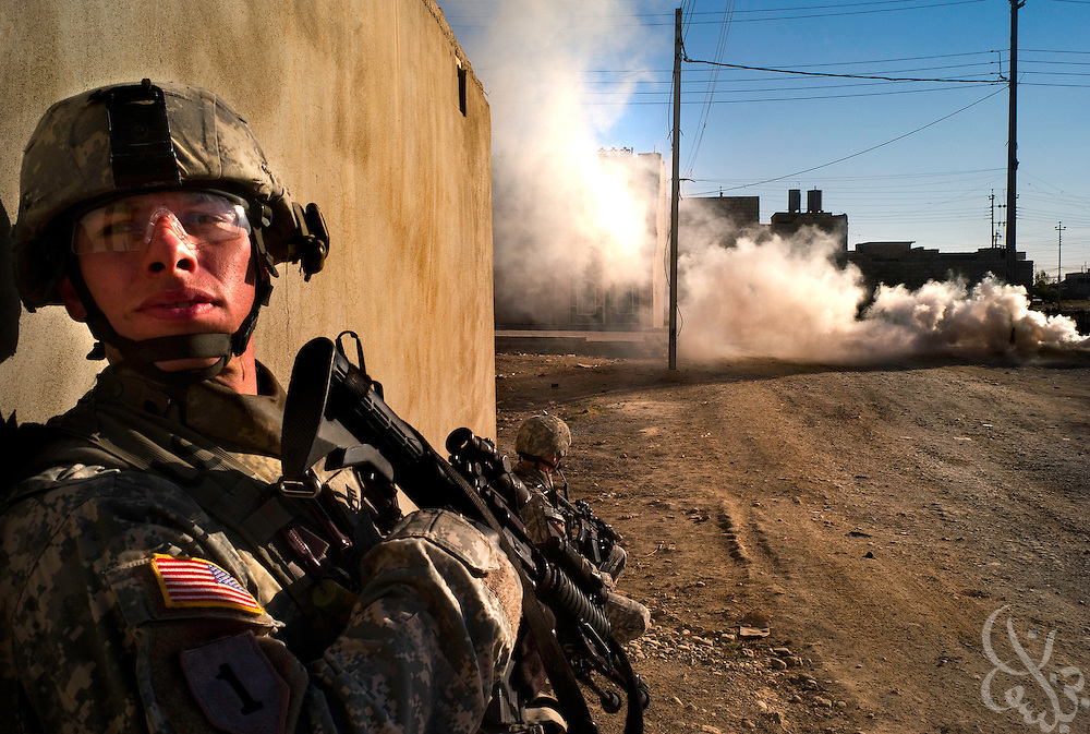 U.S. Army 1st Cavalry Division 2-7 soldiers take cover against a wall as a smoke grenade is used behind them to help conceal their position from view during an October 18, 2007 mission in Mosul, Iraq. U.S. soldiers usually conduct joint U.S.-Iraqi raids, however also undertake unilateral missions too depending on the level of importance of the target, sensitivity of the mission, or time limitations.