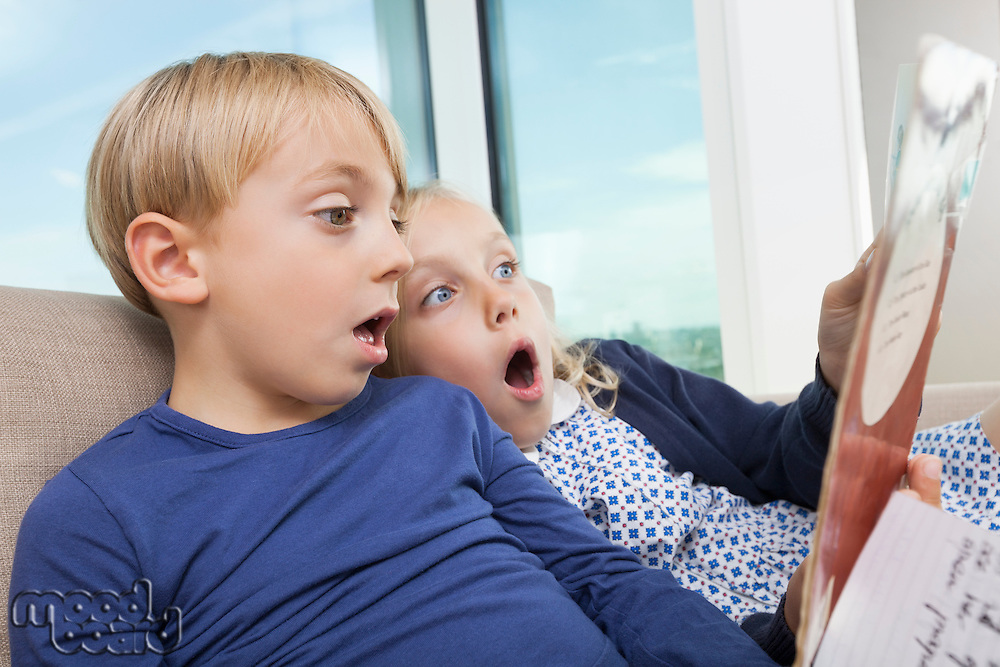 Shocked brother and sister reading storybook at home