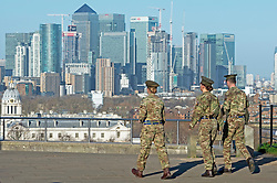© Licensed to London News Pictures. 08/01/2019. Greenwich, UK. Three soldiers walking in Greenwich Park with Blue sky over Canary Wharf, Winter sunny weather at Greenwich Park,Greenwich today but temperatures at set to plunge. Photo credit: Grant Falvey/LNP