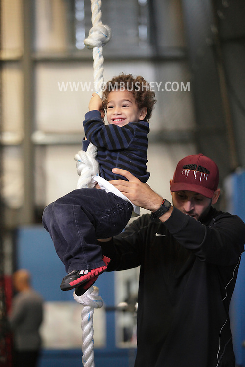 Chester, New York - Frozen Ropes instructor Tom Bordanaro helps a boy on the climbing rope during the first anniversary open house celebration at The Rock Sports Park on Saturday, Nov. 12, 2011.