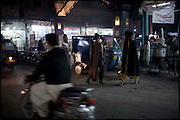 "Transvestites walk on the main road of Bazar. They usually buy cosmetics products to use for the daily job, in the red lights district. Evening in Lahore, Pakistan on Wednesday, December 03 2008.....""Not men nor women"". Just Hijira, Kusra. Painted lips, Kajal surrounding their eyes and colourful veils..Pakistan is today considered a strongly, foundamentalist as well, islamic country. But under its reputation, above all over the talebans' continuos advancing, stirs a completely extraneous world, a multiethnic mixed society. Transvestites make part of it, despite this would not be admitted by a strict law. Third gender, the Hijira are born as men (often ermaphrodites) or with an ambiguous genital situation, and they have their testicles and penis removed through a - often brutal - surgical operation. The peculiarity is that this operation does not contemplate the reconstruction of a female organ. This is the reason why they are not considered as men nor women, just Hijira. They are often discriminated, persecuted  and taxed with being men prostitutes in the muslim areas. The members of this chast perform dances during celebrations, especially during weddings, since it is anciently believed that an EUNUCO's dance and kiss in the wedding day brings good luck to the couple's fertility...To protect the identities of the recorded subjects names and specific .places are fictionals."