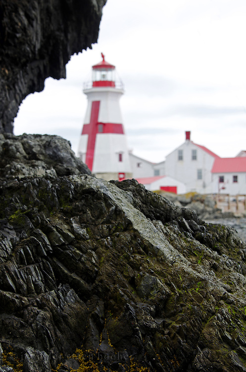 A dark rock outcrop frames the East Quoddy Lighthouse (also known as the Head Harbor Light.)