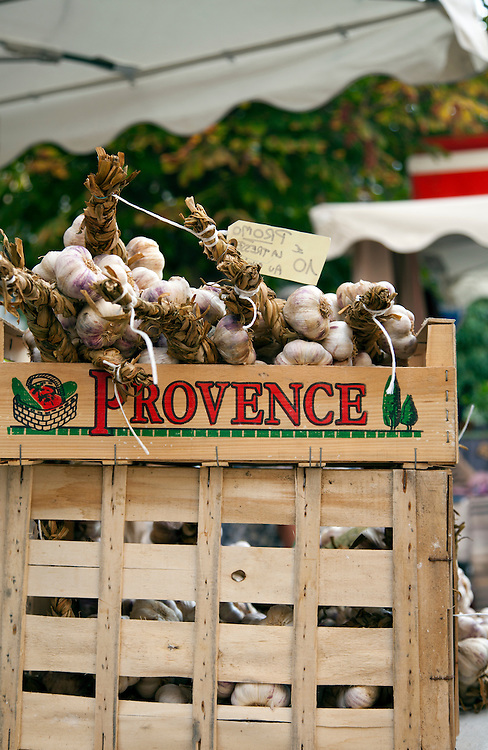Stalks of garlic along with vintage clothing, toys, and antiques share sidewalk space with amazing food and working artists during the Sunday flea markets for which the town of L'Isle-sur-la-Sorgue is famous.