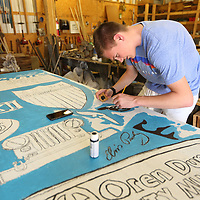 Reed McNeal starts to paint in the details of te Elvis silhouette from the Tupelo Aquatic Center that they have added to their mural.