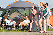 The sun continues to shine on the second day of Glastonbury Festival after it opened it's gates yesterday for the early arrivals. Approximately 170,000 revellers are set to turn up to the festival which is hosting a number of headliners including Kanye West and Alt J. <br /> Pictured: Festival goers enjoy the sunshine outside their tent on day two.