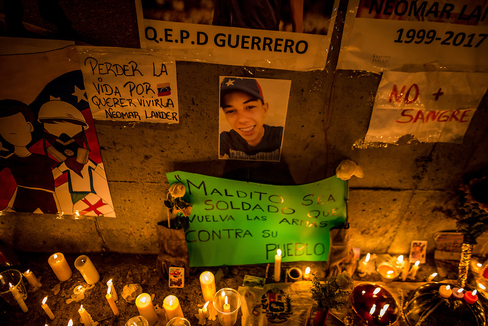 """CARACAS, VENEZUELA - JUNE 8, 2017: A photo of Neomar Lander, 17, is surrounded by candles and momentos that members of """"The Resistance"""" made around the blood-stained spot on the road where Mr. Lander, was killed by security forces during a protest in Caracas. Johan Caldera, a close friend of Mr. Lander said he is even more determined to protest since his friend was killed.  """"Now, I have no fear - because I already lost the fear I had, and the respect for the military. The little respect I had, is gone. Now, the real soldiers of Venezuela wear rags on their faces, they wear a glove and they they don't use grenades - they use stones, they use their will, and they use their balls to go out into the street."""" He said he had discussed with Neomar the possibility of being killed during the protests, """"and he [Neomar] told me: brother, if I die - if I lose my life during a protest, I don't want everyone to stop marching, I want them to march double and keep going to the street for a week, every single day, day and night without fear.""""  PHOTO: Meridith Kohut"""