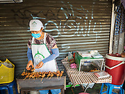 29 JUNE 2015 - BANGKOK, THAILAND:  A grilled meat vendor who has set up in front of a closed shophouse in the Bang Chak Market in Bangkok. The Bang Chak Market serves the community around Sois 91-97 on Sukhumvit Road in the Bangkok suburbs. About half of the market has been torn down, vendors in the remaining part of the market said they expect to be evicted by the end of the year. The old market, and many of the small working class shophouses and apartments near the market are being being torn down. People who live in the area said condominiums are being built on the land.    PHOTO BY JACK KURTZ