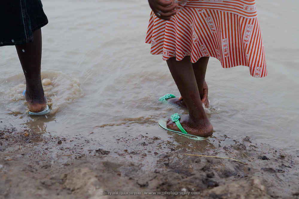 Alimata Ouedraogo (18) washes mud off her feet after she and her sisters collected water from a dam in Koala, Burkina Faso on 1 March 2014. The girls typically make three round trips every day, filling 17 jerry cans each time, with each trip taking over an hour.