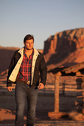 All American hot man walking on a ranch at sunset