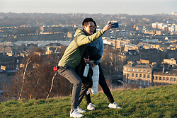 Edinburgh, Scotland, UK. 26 February, 2019. Tourists enjoy view of Leith from Calton Hill in Edinburgh after a warm clear day , Edinburgh, Scotland, UK