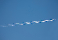 Airplane with vapour trail in the sky over Dublin Ireland