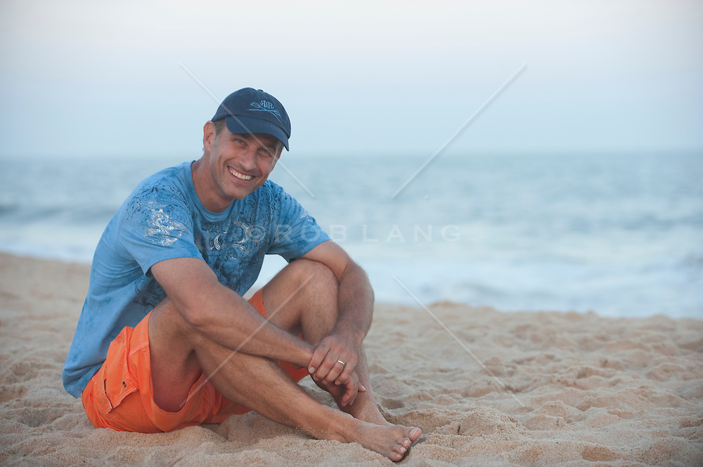 Handsome Man smiling and relaxing on the beach in East Hampton, NY
