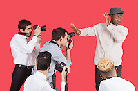 Young male celebrity shielding face from photographers over red background