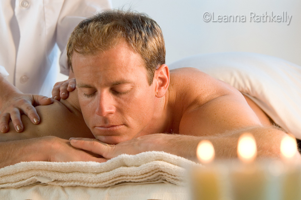 Man getting a massage relaxes, candles in the foreground.