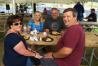Julie Dozois and Mark Heon sit down to lunch with brisket and chicken wings joined by Cathy Bozeman and Roger Heon with the pulled pork sandwiches during Gunstock Mountain's Brew and BBQ Fest on Saturday.  (Karen Bobotas/for the Laconia Daily Sun)