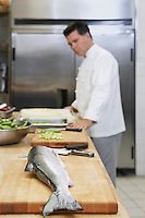 Male chef in kitchen focus on salmon in foreground