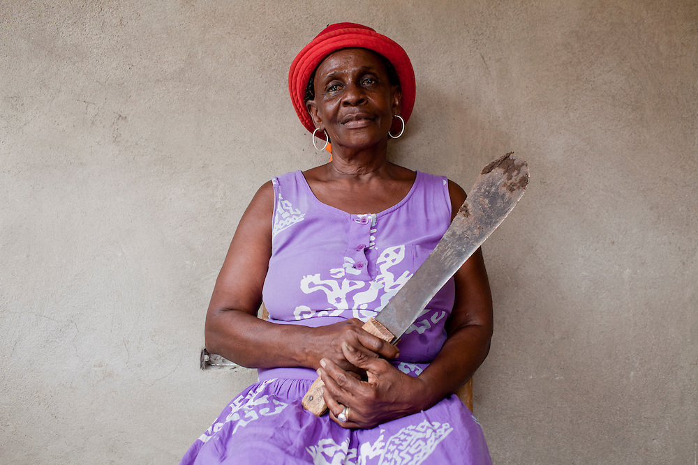A woman poses for a portrait with a machete on July 16, 2010 in Corail Henri, Haiti.