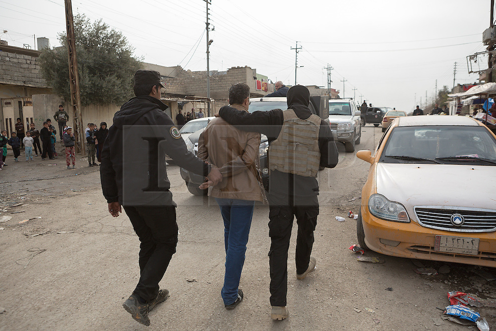 Licensed to London News Pictures. 13/02/2017. Mosul, Iraq. Local residents watch as officers of the Iraqi National Security Service lead away a medical worker, accused of providing information on civilian casualties to the Islamic State, during a raid on a clinic in east Mosul.<br /> <br /> The Jihaz Al-Amin Al-Watani, roughly translated as the National Security Service or NSS, are a secretive Iraqi agency that works under the responsibility of the Ministry of Interior. Since the liberation of eastern Mosul in January 2017 the NSS have been actively hunting down ISIS members who stayed behind to continue terrorism as part of sleeper cells and residents who worked with the group during its two year occupation. Recruiting from across the country agency is responsible for internal security inside Iraq and has a broad remit to investigate and arrest everything from terrorists and foreign spies to financial criminals and drug traffickers. Photo credit: Matt Cetti-Roberts/LNP