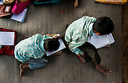 13th March 2014, Shakarpur, New Delhi, India. Children study at a makeshift school under a metro bridge near the Yamuna Bank Metro station in Shakarpur, New Delhi, India on the 13th March 2014<br /> <br /> Rajesh Kumar Sharma (born 01/02/1970), started this makeshift school in 2011. Six mornings a week he teaches underprivileged children for three hours while his younger brother replaces him at his general store in Shakarpur. His students are children of labourers, rickshaw-pullers and farm workers. This is the 3rd site he has used to teach under privileged children in the city, he began in 1997. <br /> <br /> PHOTOGRAPH BY AND COPYRIGHT OF SIMON DE TREY-WHITE<br /> + 91 98103 99809<br /> email: simon@simondetreywhite.com<br /> photographer in delhi<br /> journalist