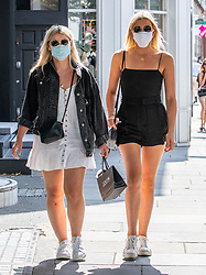 © Licensed to London News Pictures. 22/07/2020. London, UK. A shopper enjoys the warm sunshine on the King's Road in Chelsea despite the stuffy masks as weather forecasters predict 26c today as Londoners get ready for Friday when masks become compulsory in shops in England. Photo credit: Alex Lentati/LNP