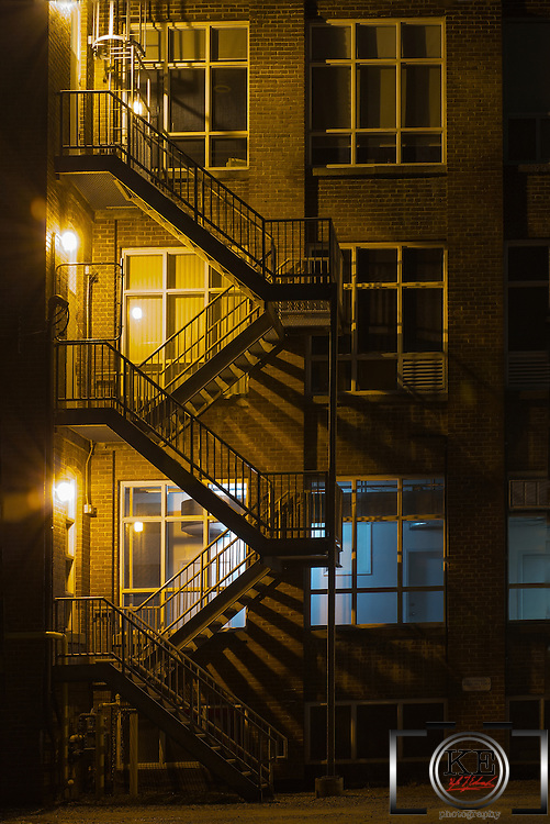 A fire escape with interesting lighting, both from the external  security lights filtering through the stairs and a blue security light in the building.