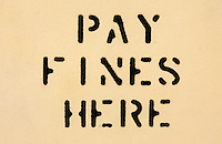 A stenciled sign that reads pay fines here