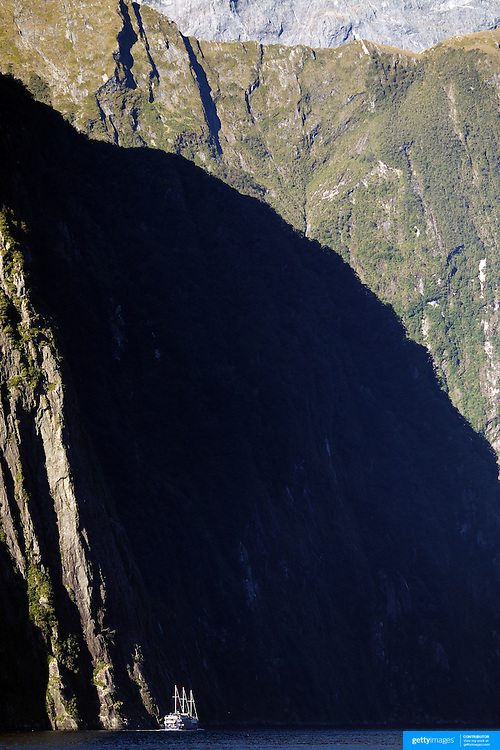 A Real Journey's tourist cruise ship dwarfed by the steep cliff faces of Milford Sound, South Island, New Zealand. .Milford Sound (Piopiotahi in Ma¯ori) is a fjord in the south west of New Zealand's South Island, within Fiordland National Park and the Te Wahipounamu World Heritage site. It has been judged the world's top travel destination and is acclaimed as New Zealand's most famous tourist destination..Milford Sound runs 15 kilometres inland from the Tasman Sea at Dale Point - the mouth of the fiord - and is surrounded by sheer rock faces that rise 1,200 metres (3,900 ft) or more on either side. Among the peaks are The Elephant at 1,517 metres (4,977 ft), said to resemble an elephant's head and The Lion, 1,302 metres (4,272 ft), in the shape of a crouching lion. Lush rain forests cling precariously to these cliffs, while seals, penguins, and dolphins frequent the waters and whales can be seen sometimes..Milford Sound sports two permanent waterfalls all year round, Lady Bowen Falls and Stirling Falls. After heavy rain many hundreds of temporary waterfalls can be seen running down the steep sided rock faces. .The beauty of this landscape draws thousands of visitors each day, with between 550,000 and 1 million visitors in total per year. This makes the sound one of New Zealand's most-visited tourist spots, and also the most famous New Zealand tourist destination.  Milford Sound, New Zealand. 29th April 2011. Photo Tim Clayton