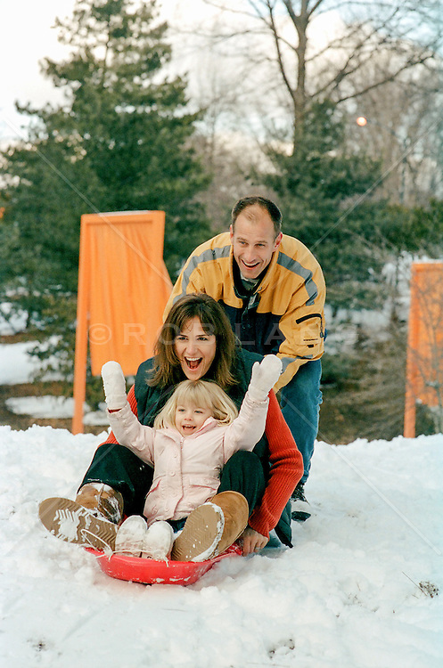 family of three enjoying a sled in the snow