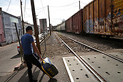 Pedestrians wait as a Union Pacific freight train carrying goods from Mexico crosses from Nogales, Sonora, Mexico, in to Nogales, Arizona, USA, at the DeConcini Customs Inspection Station as part of NAFTA or the North American Free Trade Agreement.