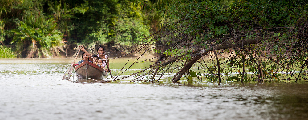 An Embera family traveling on the Rio Sambu, Panama.