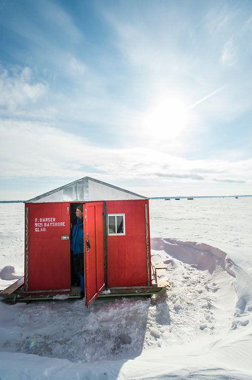 """An ice fisherman looks out from a larger """"sleeper"""" ice fishing shelter featuring bunks for sleeping in on Little Bay de Noc near Gladstone, Michigan."""