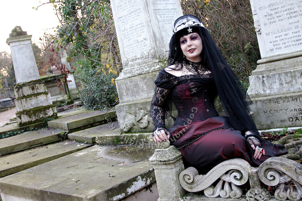 Cecile, a 31-year-old French national is posing while sitting on a grave during a  cemetery tour organised by the Vampyre Connexion on Sunday, 2 December, 2006, in Nunhead Cemetery, South London, England. The Vampyre Connexion is the largest and most active of all the vampire groups in the United Kingdom, counting more than 100 members that for years have gathered regularly in London to share their common love for vampires and the Dark side of life. The Connexion raised from the hashes of the Vampyre Society, the first vampire appreciation group in 1995. The group believe in the fantasy of vampires and such creatures and live it to the full. Its  roots are to be found in the legends of Bram Stokerís Dracula. The group prints its own magazine, ëDark Nightsí featuring drawings, poetry, stories, photography and events. All of the members dress very peculiar clothing, and this is a very important part of the life of the group; it is respected with pride, taste and accuracy for the detail. Most like to dress to be elegant in a range of styles from regency to Victorian, some sew their own. In addition members visit art galleries, cemeteries, churches and cathedrals, attend gigs and concerts, and hold their own parties throughout the year, Halloween being the biggest and scariest one. Membership is open to all, the only qualification: being a love of all things Vampyric.**ItalyOut**