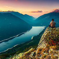 Man sitting on the edge of the mountain rock