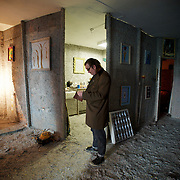 Ireland: Irish artist Frank Buckley stands in the main hall of his Billion Euro House art installation in central Dublin. ..Worthless euros, taken out of circulation and shredded by Irelands Central Bank, formes the interior walls of an apartment that Mr. Buckley does not own in a building left vacant by the countrys economic ruin...The artist decided to call the apartment  built from thousands of bricks of shredded, decommissioned cash (each brick contains, roughly, what used to be 50,000 euros)  the Billion Euro House. He reckons that about 1.4 billion euros actually went into it, but the joke, of course, is that it is worth simultaneously so much and so little...A large gravestone beside the main door, announces that Irish sovereignty died in 2010, the year that the government accepted an international bailout so larded with onerous conditions that the Irish will be paying for it for years to come. (Paulo Nunes dos Santos/Polaris)