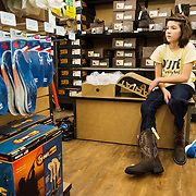 Ladlie sits on a bench at the Tractor Supply Co. store in Troy, Mo., while her mother searches for different pair of boots for her to wear to an upcoming Future Farmers of America event..