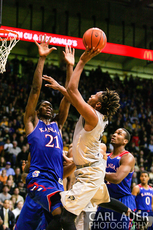 December 7th, 2013:  Colorado Buffaloes sophomore forward Xavier Johnson (2) floats a shot over Kansas Jayhawks freshman center Joel Embiid (21) in the second half of action in the NCAA Basketball game between the Kansas Jayhawks and the University of Colorado Buffaloes at the Coors Events Center in Boulder, Colorado