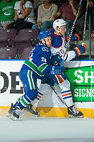 PENTICTON, CANADA - SEPTEMBER 11: Jakob Stukel #34 of Vancouver Canucks checks Luke Coleman #70 of Edmonton Oilers into the boards on September 11, 2017 at the South Okanagan Event Centre in Penticton, British Columbia, Canada.  (Photo by Marissa Baecker/Shoot the Breeze)  *** Local Caption ***