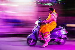 A night time street life motion-blur scene of a girl in a sari on a motorbike, Jodphur, Rajasthan, India,