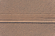Aerial view of wildlife fence and its shadow falling across a gravel maintenance road, viewed from directly overhead the Tsauchab Plains of the Namib-Naukluft Park near Sossusvlei in central Namibia, southwest Africa.