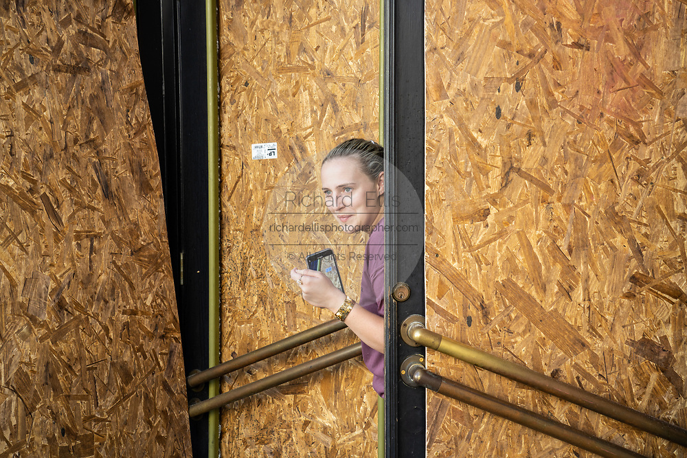 Charleston, United States. 31 May, 2020. A shop owner looks out from the boarded up store front along the King Street shopping district after a protest over the death of George Floyd, turned violent and destructive May 31, 2020 in Charleston, South Carolina. Floyd was choked to death by police in Minneapolis resulting in protests sweeping across the nation.  Credit: Richard Ellis/Alamy Live News