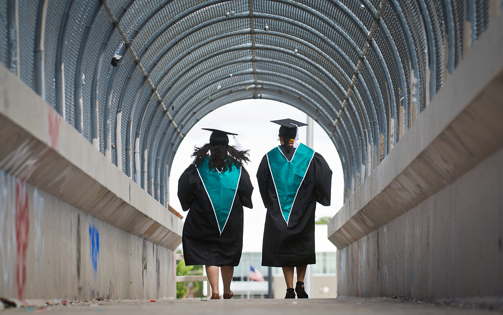 mkb051917l/metro/Marla Brose --  Del Norte High School graduates Alicia Cordero, left, and Tina Dennis cross over Montgomery NE on the pedestrial bridge after their class visited Governor Bent Elementary School in their camps and gowns to receive congratulations from the elementary school students, Friday, May 19, 2017. Del Norte, which holds their graduation Saturday evening at Tingley Coliseum, will be the last Albuquerque Public high school graduation. (Marla Brose/Albuquerque Journal)