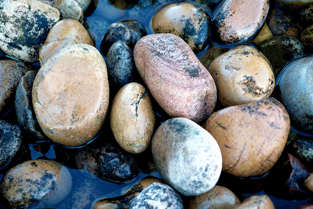 Water softly flows over creek stones
