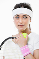 Portrait of young female tennis player against white background
