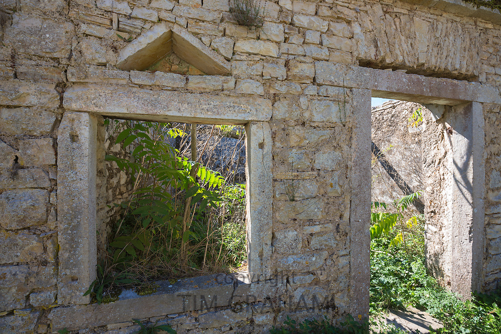Trees growing inside derelict house ruins in ancient mountain village of Old Perithia - Palea Peritheia, Corfu, Greece