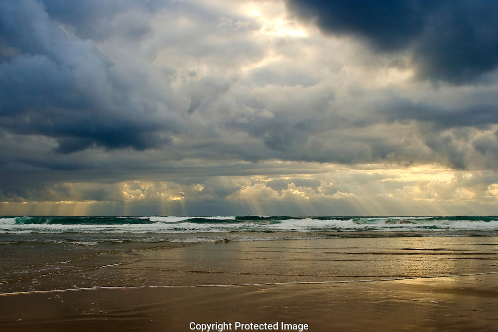 Rain drops and the last rays of sun pour through the clouds as sunset approaches the Oregon coast
